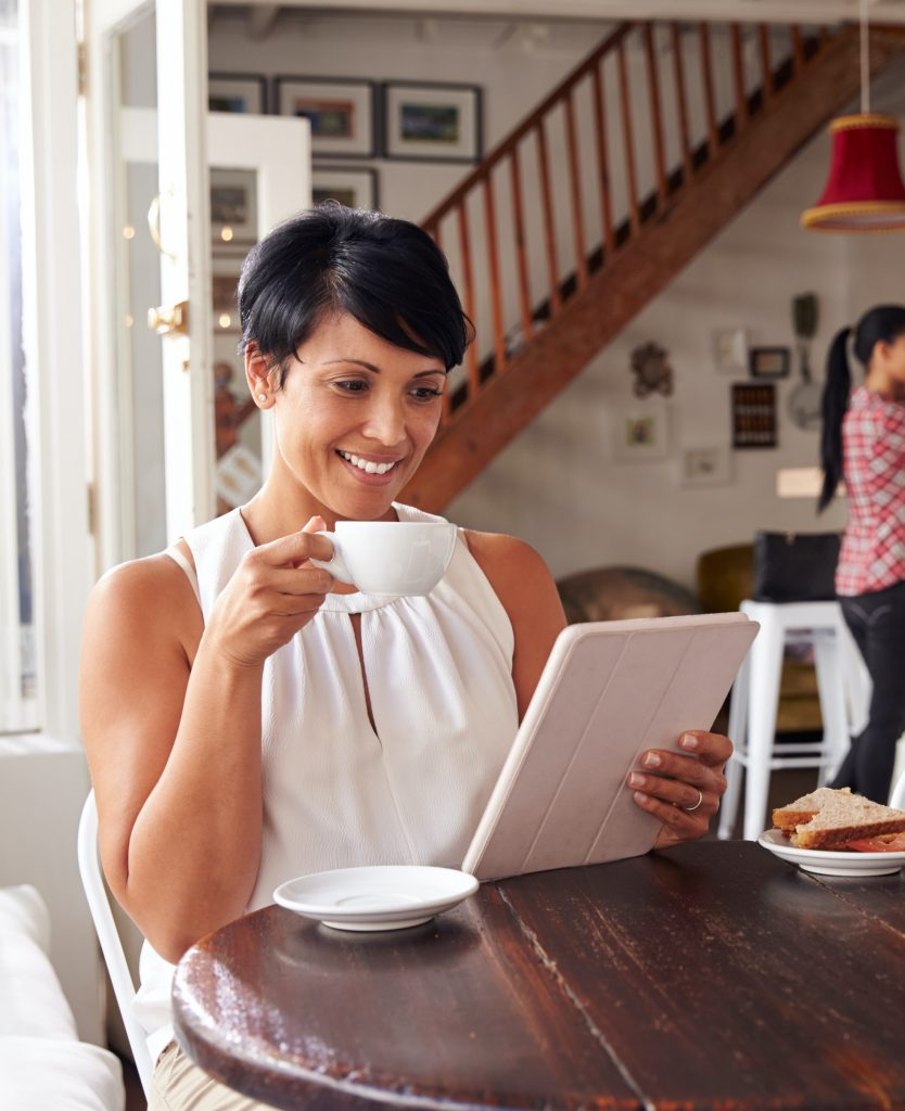 Woman at home with a cup of coffee and a tablet